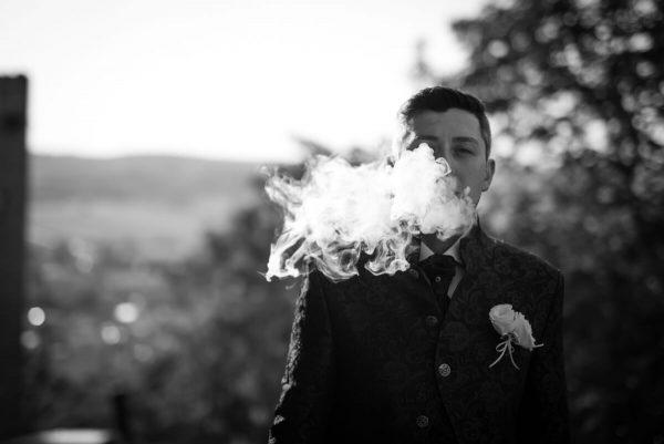 sposo mentre fuma una sigaretta facendo una nuvola di fumo