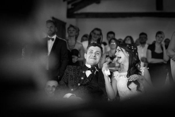 gli sposi che ridono alle foto proiettate insieme agli invitati