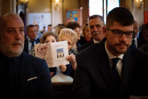 damigella guarda curiosa in braccio ai nonni durante la celebrazione del matrimonio