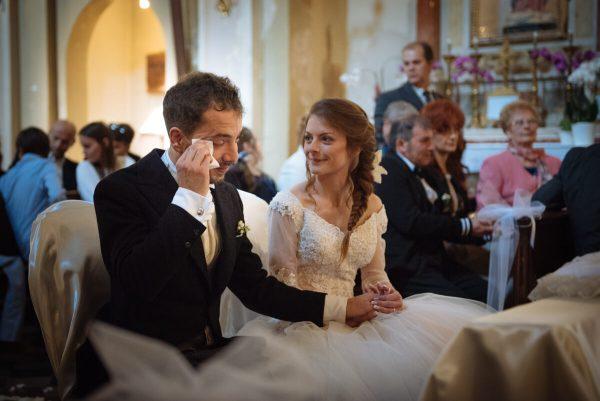 sposo che si commuove vicino la sposa all'altare durante la celebrazione