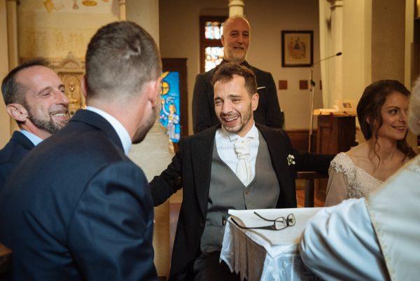 sposo commosso insieme ai testimoni e alla sposa mentre mettono le firme