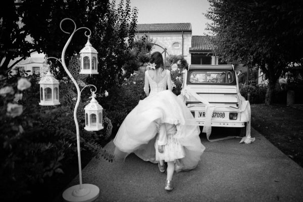 bambina che si nasconde sotto l'abito da sposa accanto la macchina d'epoca