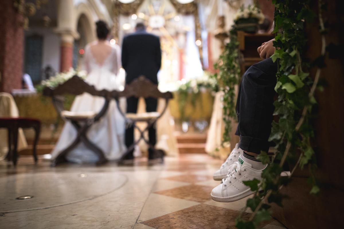 bambino seduto in chiesa al matrimonio con dettaglio sulle scarpe