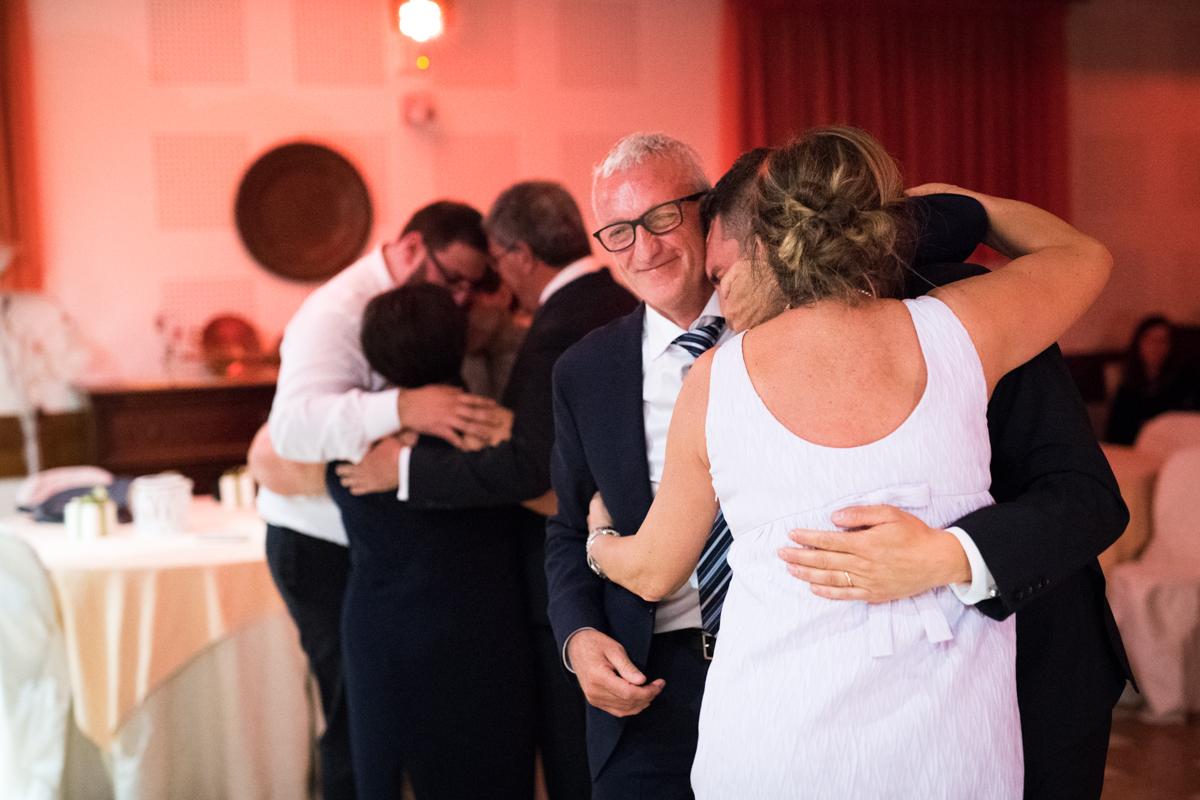 lo sposo insieme ai genitori che si abbracciano e commuovo al ballo del matrimonio