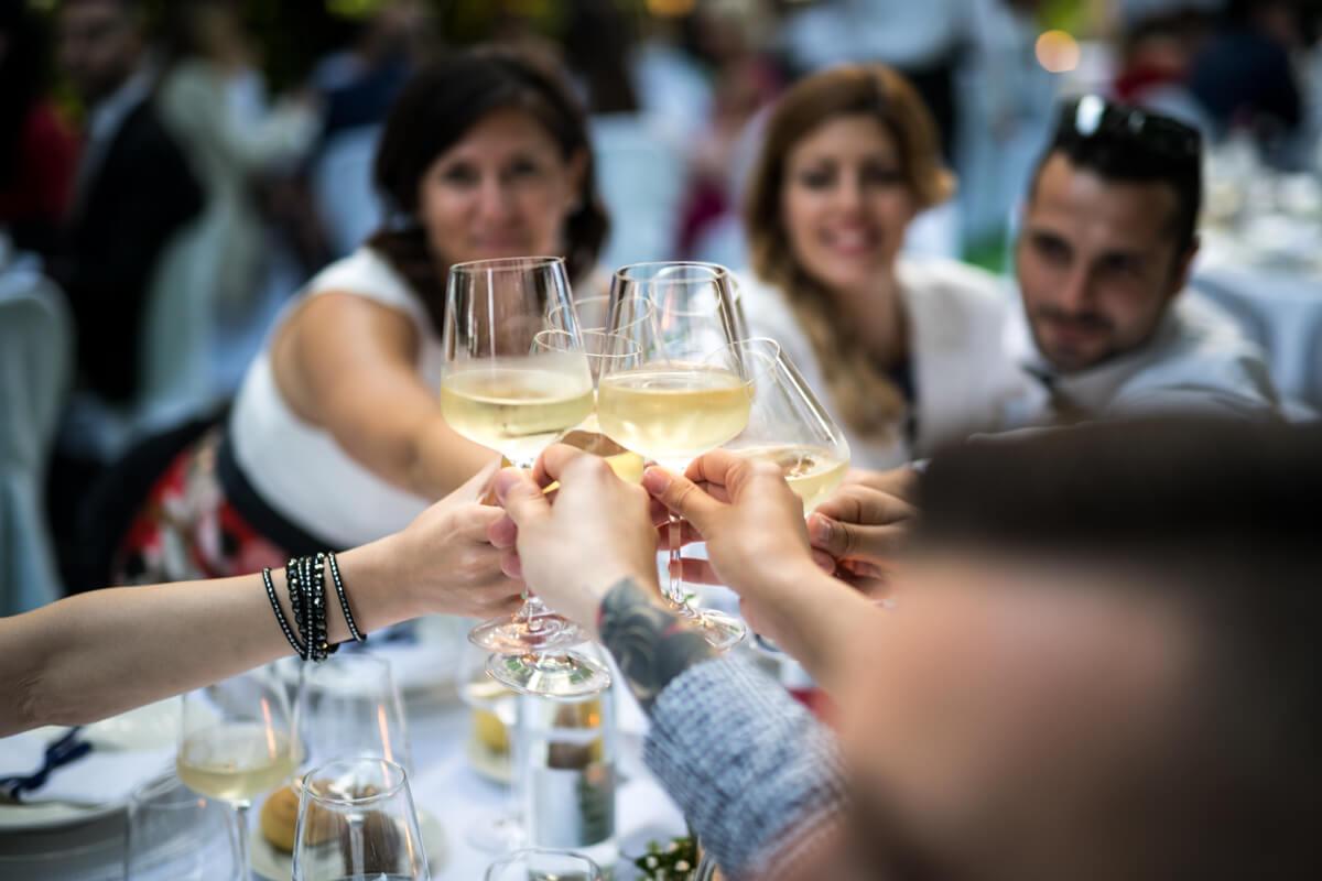 gli invitati al ricevimento del matrimonio brindano agli sposi