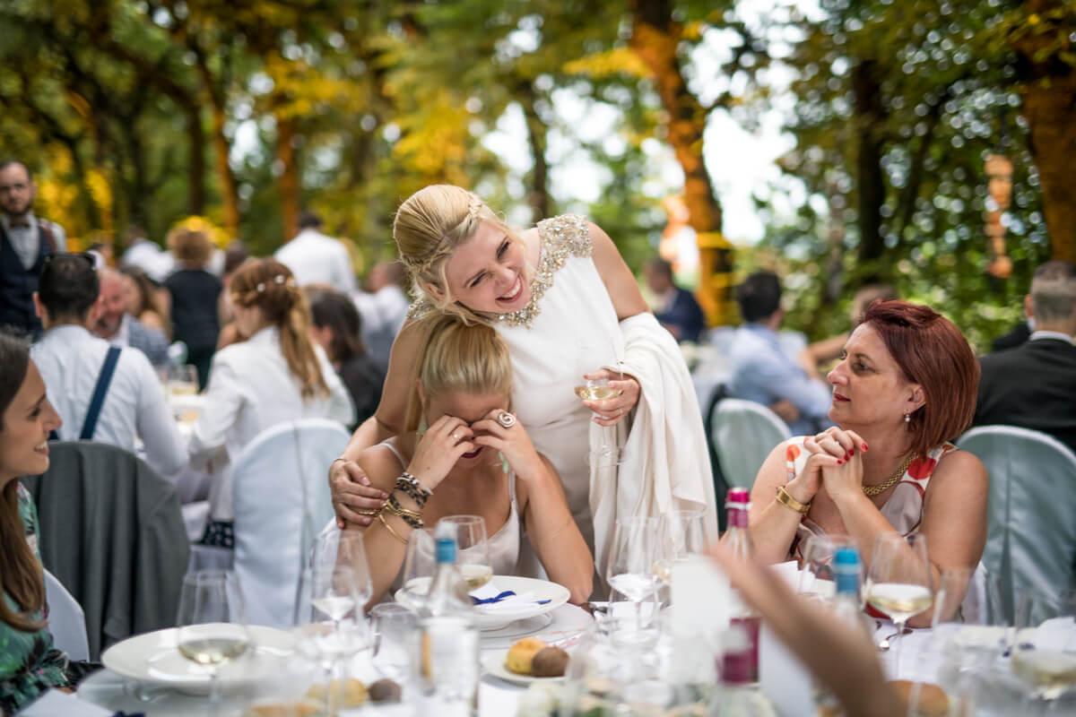 la sposa ride con delle invitate al pranzo del matrimonio