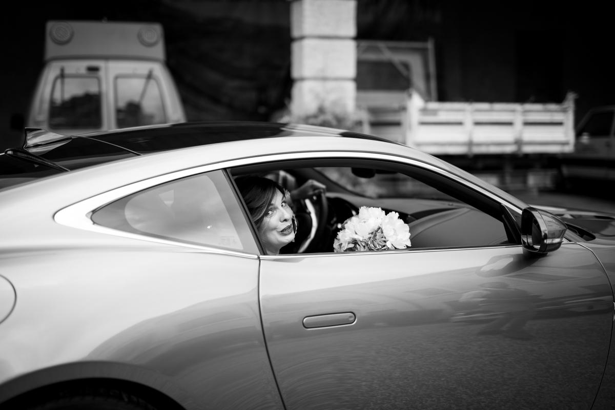 la sposa in macchina con in mano il bouquet all'arrivo al matrimonio