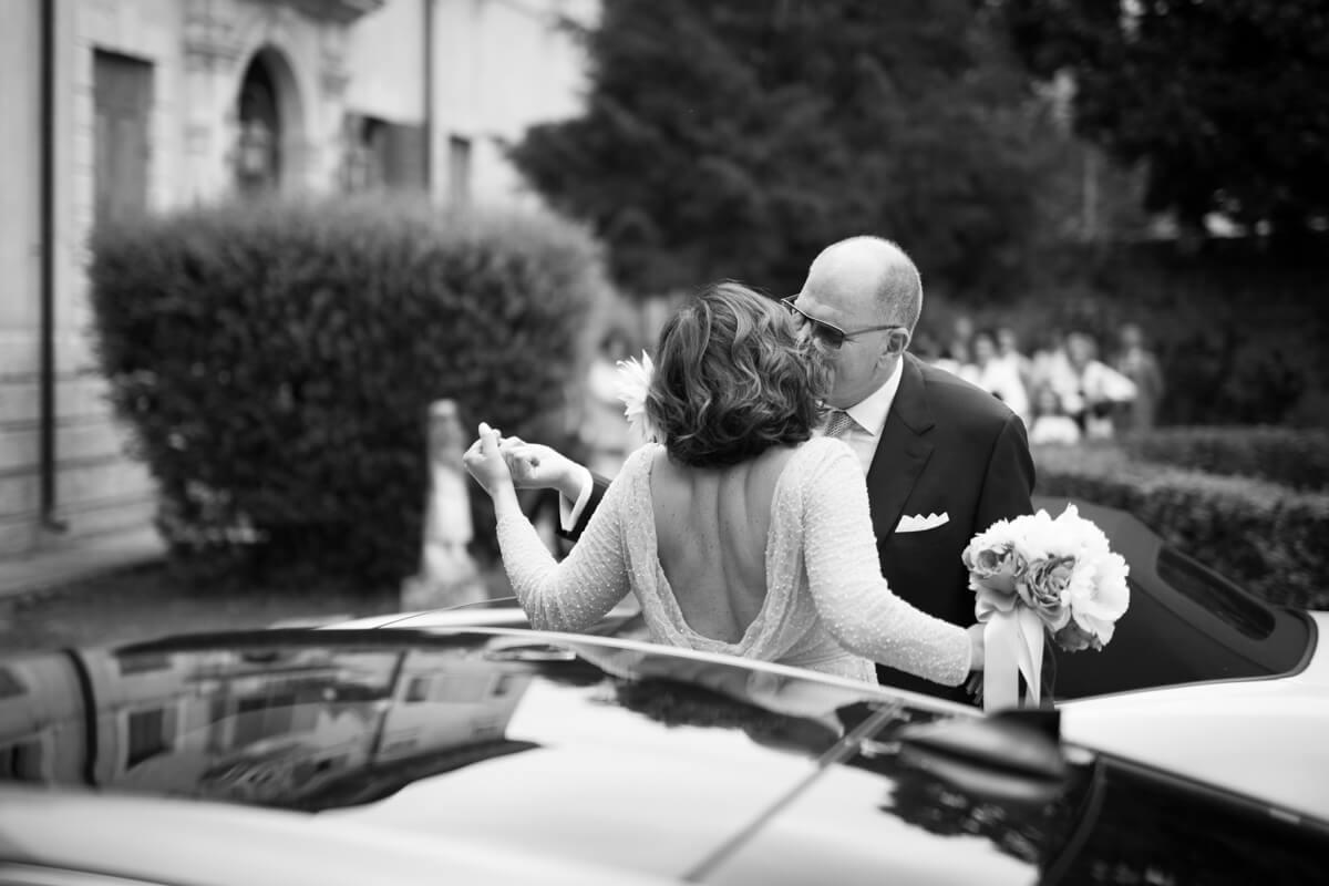 sposo bacia la sposa arrivata in macchina