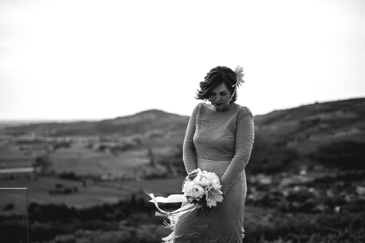la sposa in abito vintage con in mano il bouquet e come sfondo un bellissimo panorama