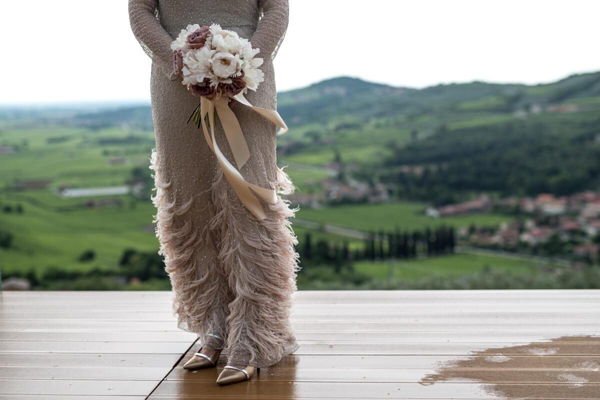 abito da sposa vintage con il bouquet e un bellissimo panorama di colline come sfondo