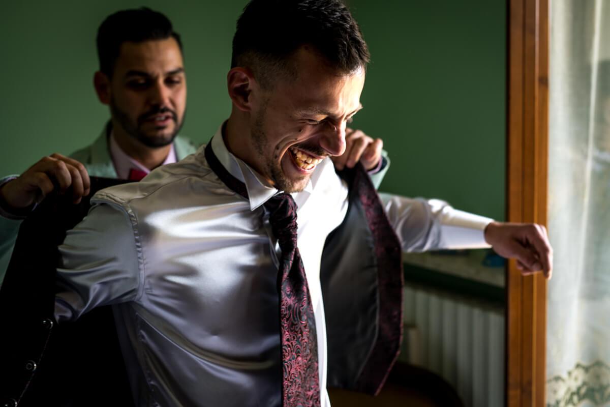 il testimone aiuta lo sposo a infilarsi la giacca prima del matrimonio