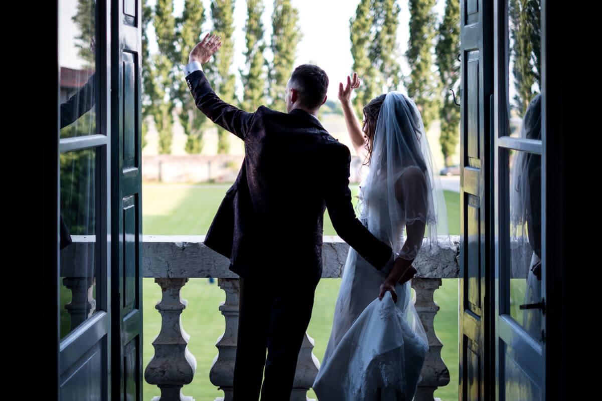 gli sposi che salutano gli ospiti dal balcone
