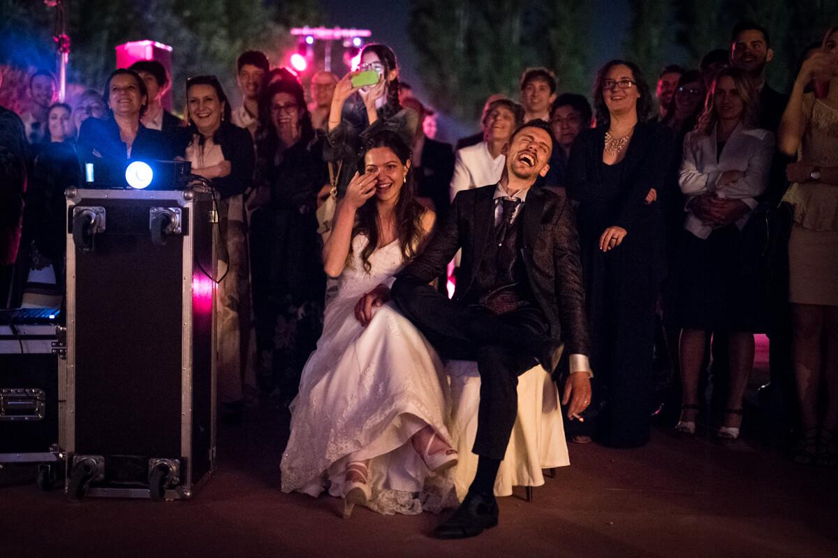 gli sposi mentre ridono ai filmati dei ricordi insieme agli invitati