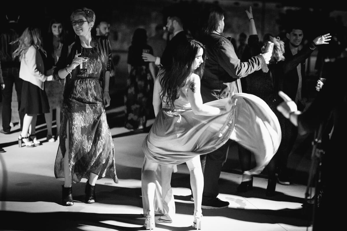 un'invitata al matrimonio mentre balla divertita muovendo il vestito