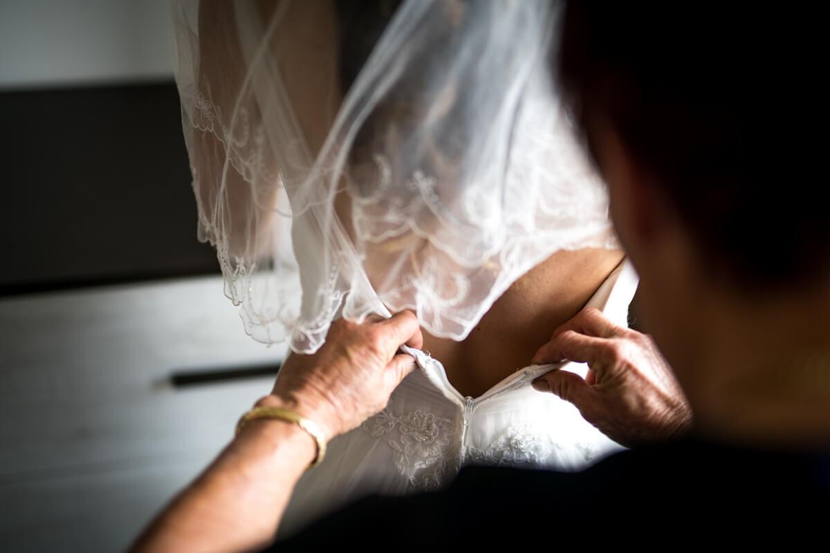 la mamma della sposa aiuta ad allacciare l'abito del matrimonio