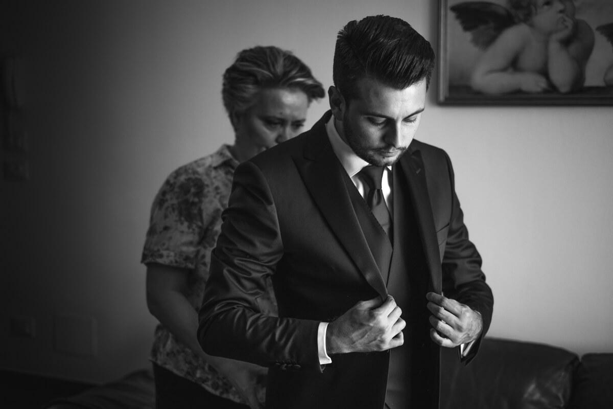 la madre dello sposo lo aiuta a sistemarsi l'abito da cerimonia
