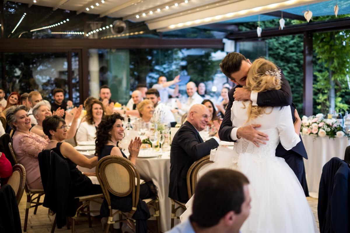 il bacio degli sposi in mezzo agli invitati al ricevimento