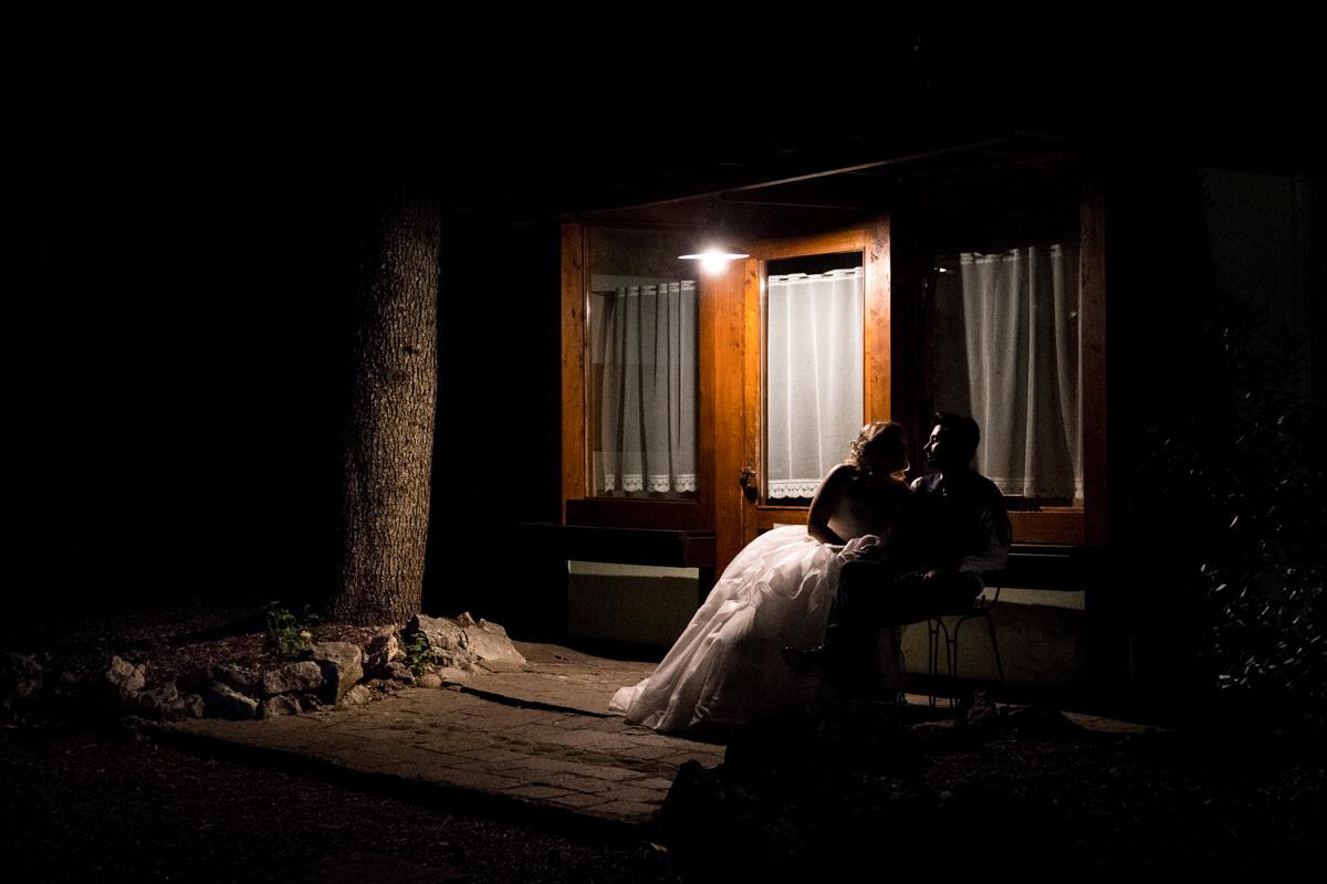 gli sposi seduti su una panchina di notte si guardano