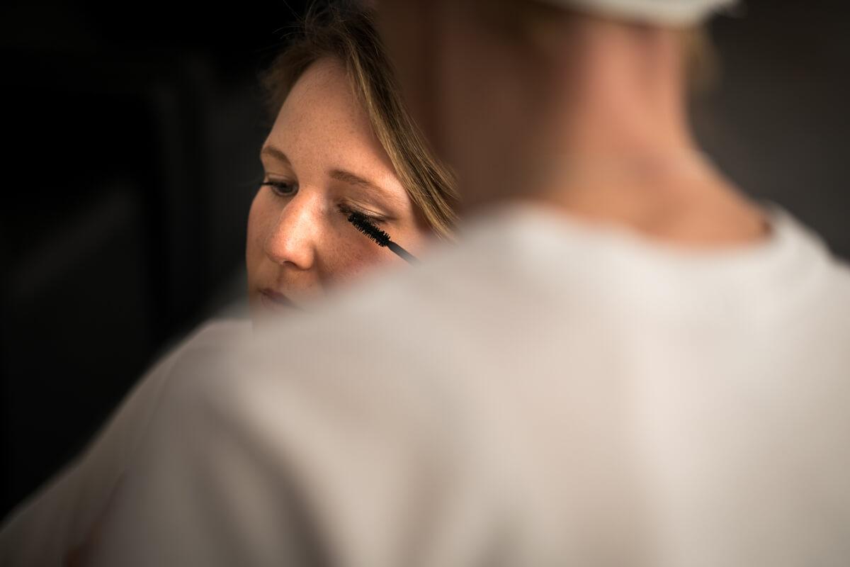 un dettaglio dell'occhio della sposa mentre viene truccato per il matrimonio