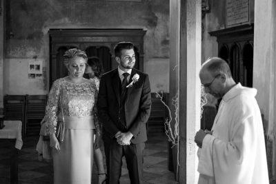 lo sposo insieme alla mamma commossa e il prete in chiesa