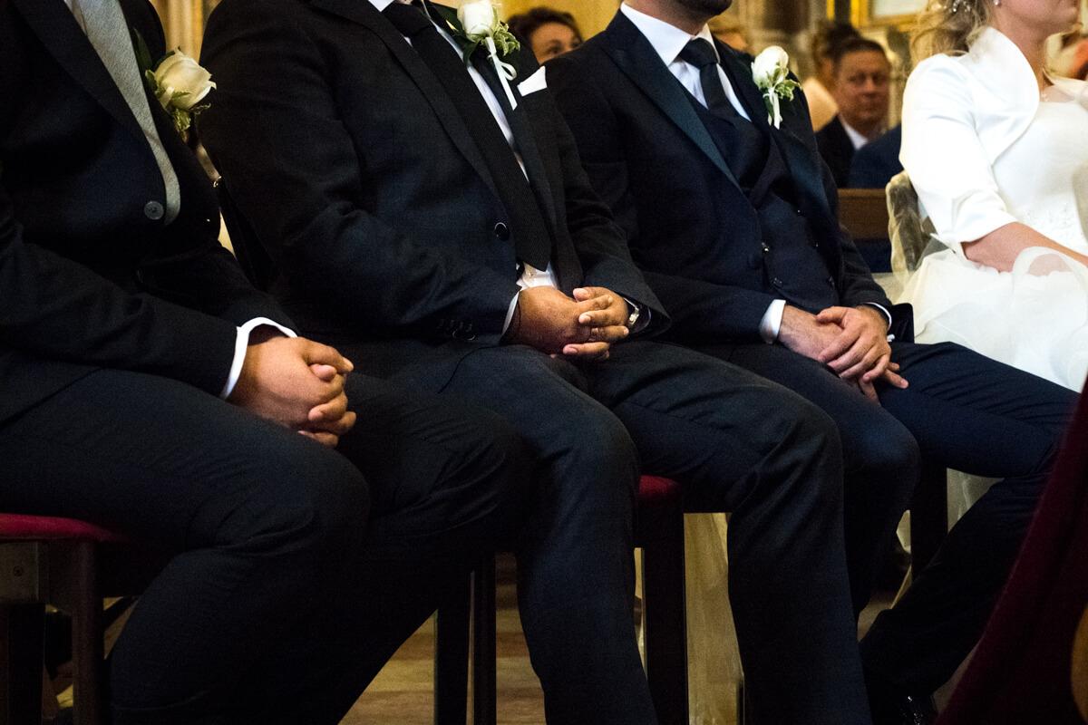 un dettaglio delle mani dei testimoni seduti in chiesa