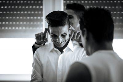 il testimone gioca con le orecchie dello sposo prima della cerimonia