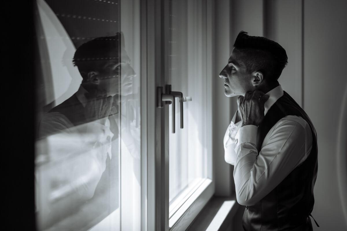 il riflesso nel vetro dello sposo mentre si sistema la camicia