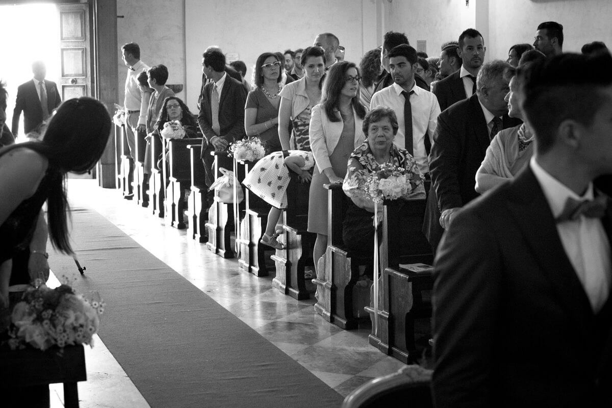 la chiesa piena di invitati con una bambina che cerca di salire sulla panca