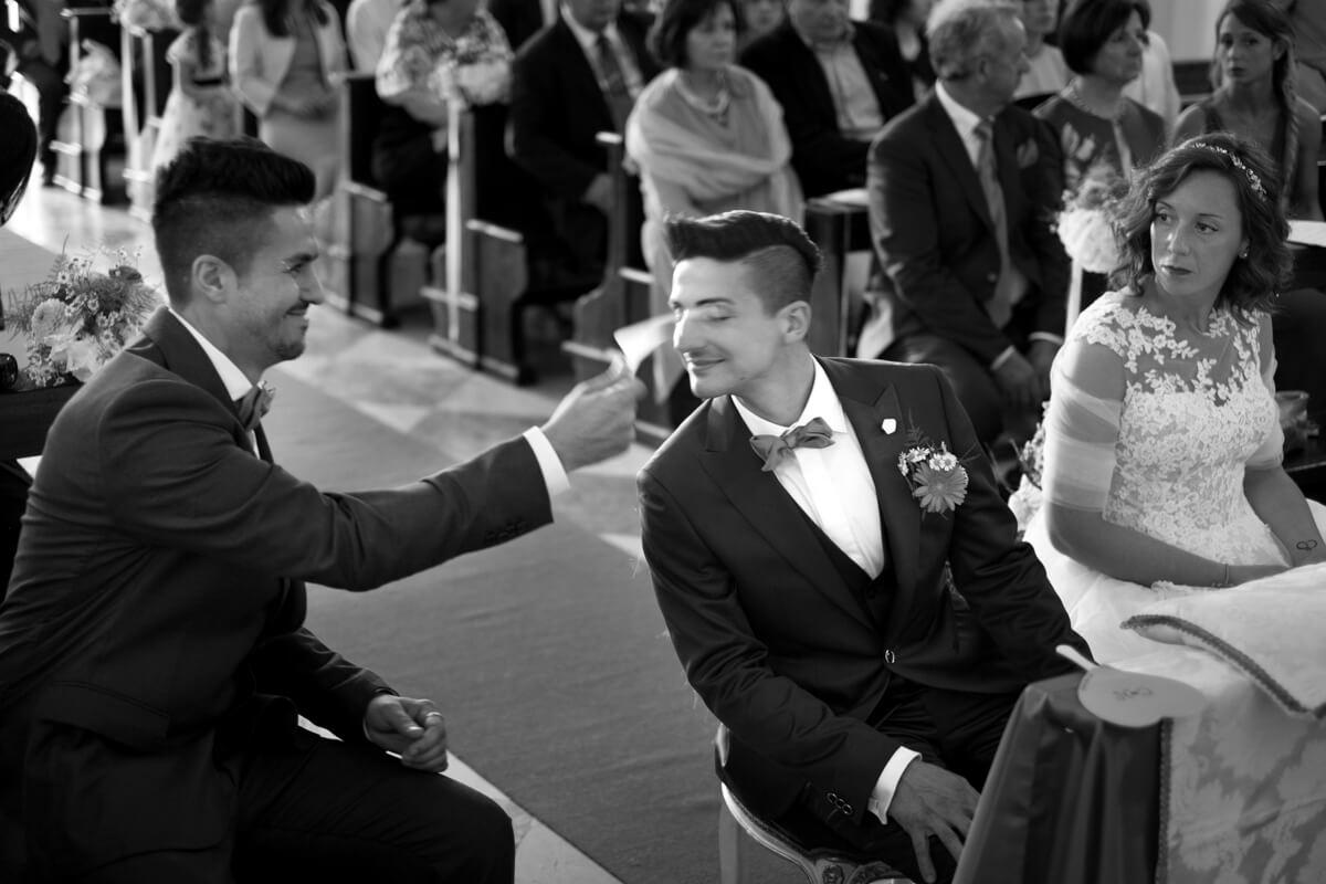 il testimone sventola un foglio verso lo sposo per fargli aria durante la celebrazione del matrimonio
