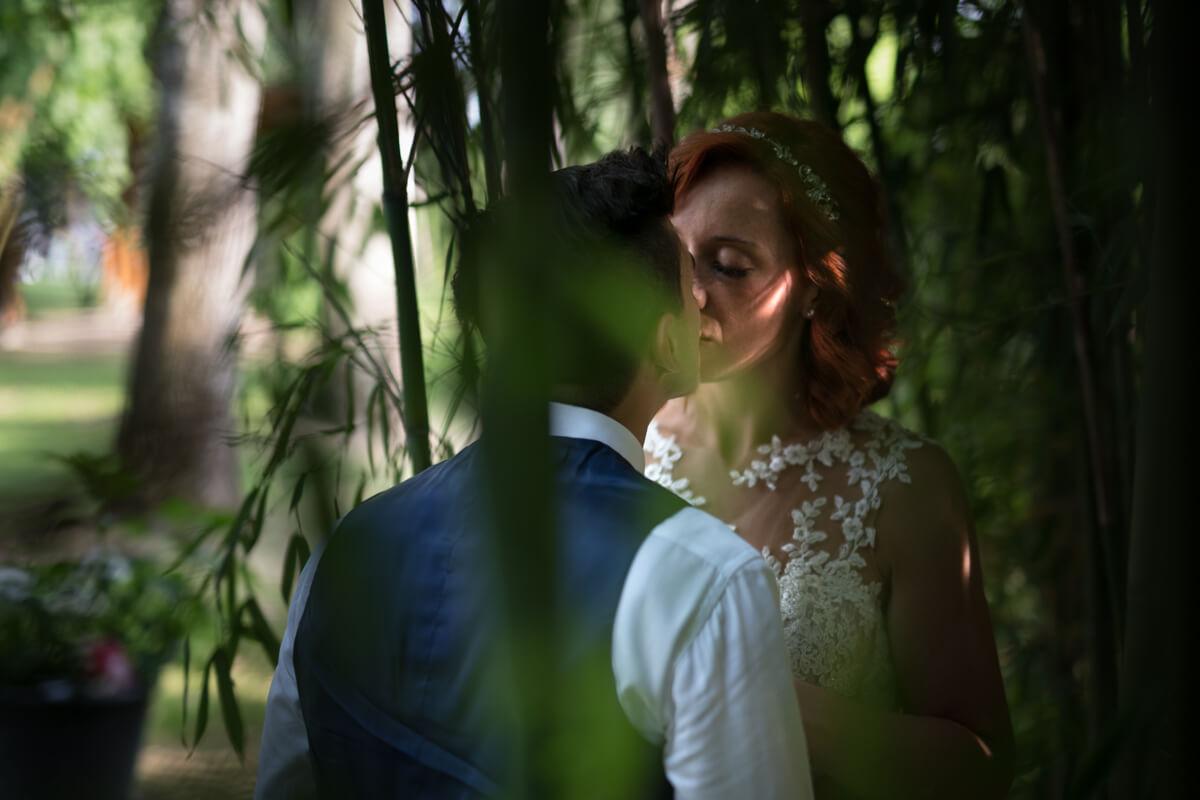 gli sposi si scambiano un bacio in mezzo alle piante