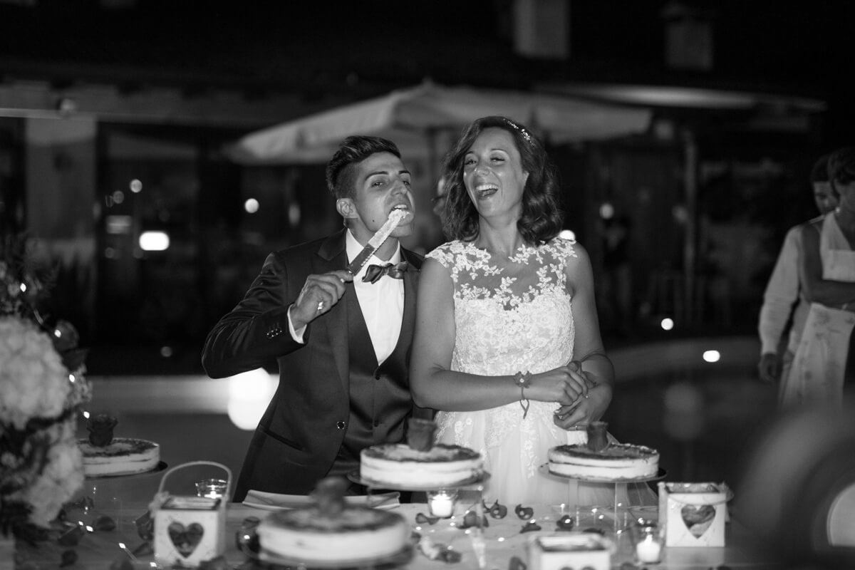 la sposa ride al momento del taglio della torta mentre lo sposo lecca il cartello sporco di panna