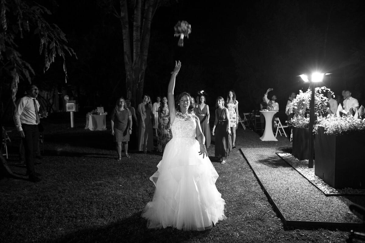 in uno scenario notturno la sposa lancia il bouquet con di dietro le invitate