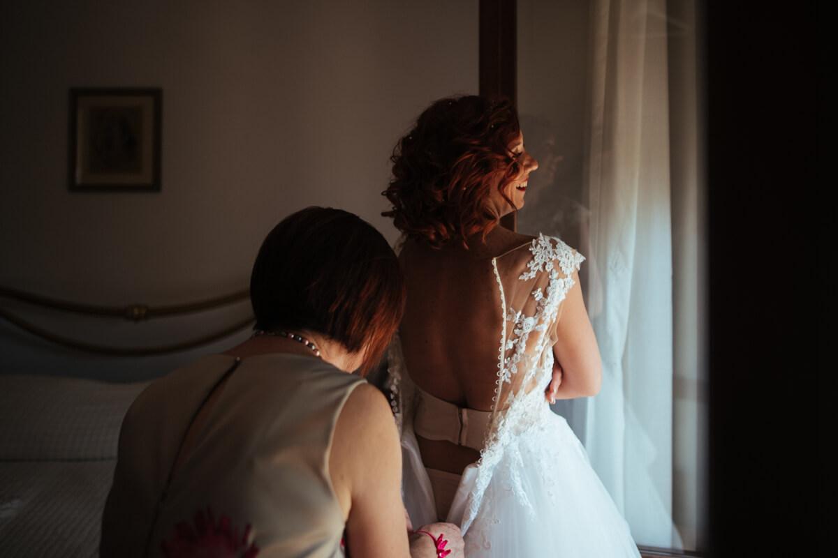 la mamma della sposa aiuta la figlia ad allacciare l'abito prima della cerimonia