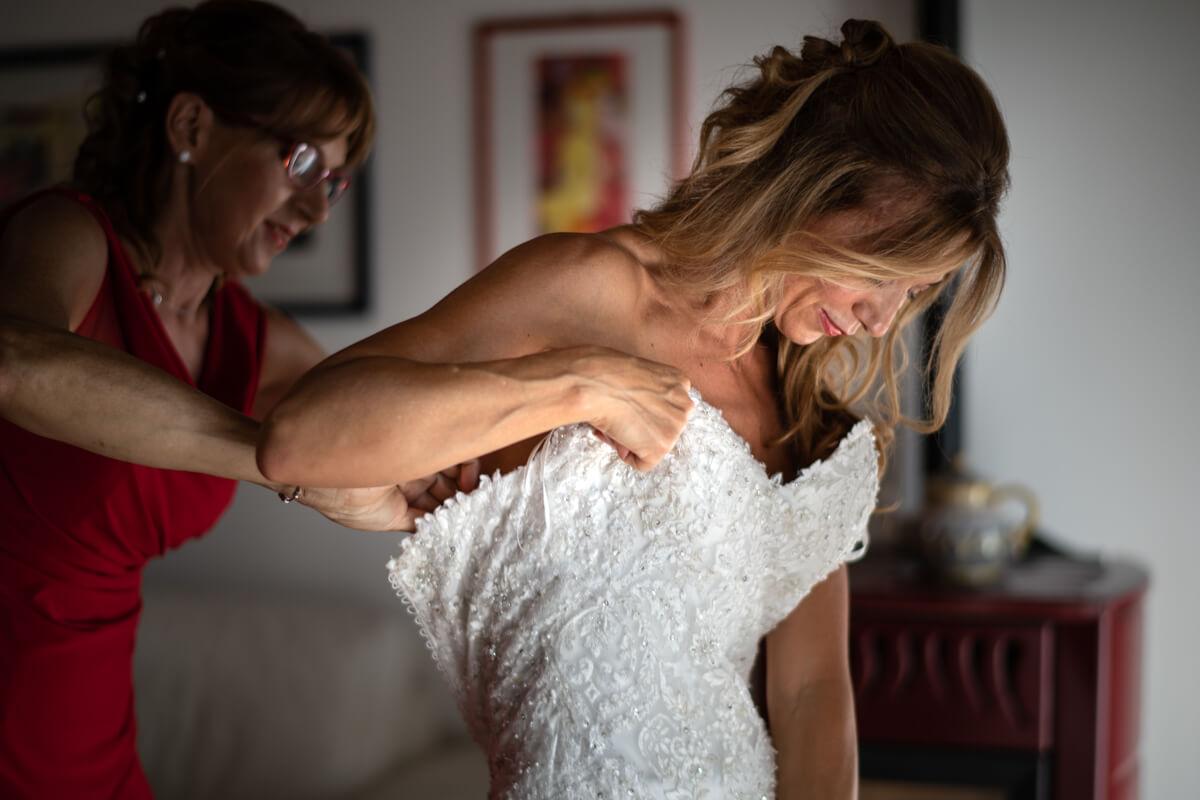la sposa aiutata da un'amica si prepara indossando l'abito per la cerimonia