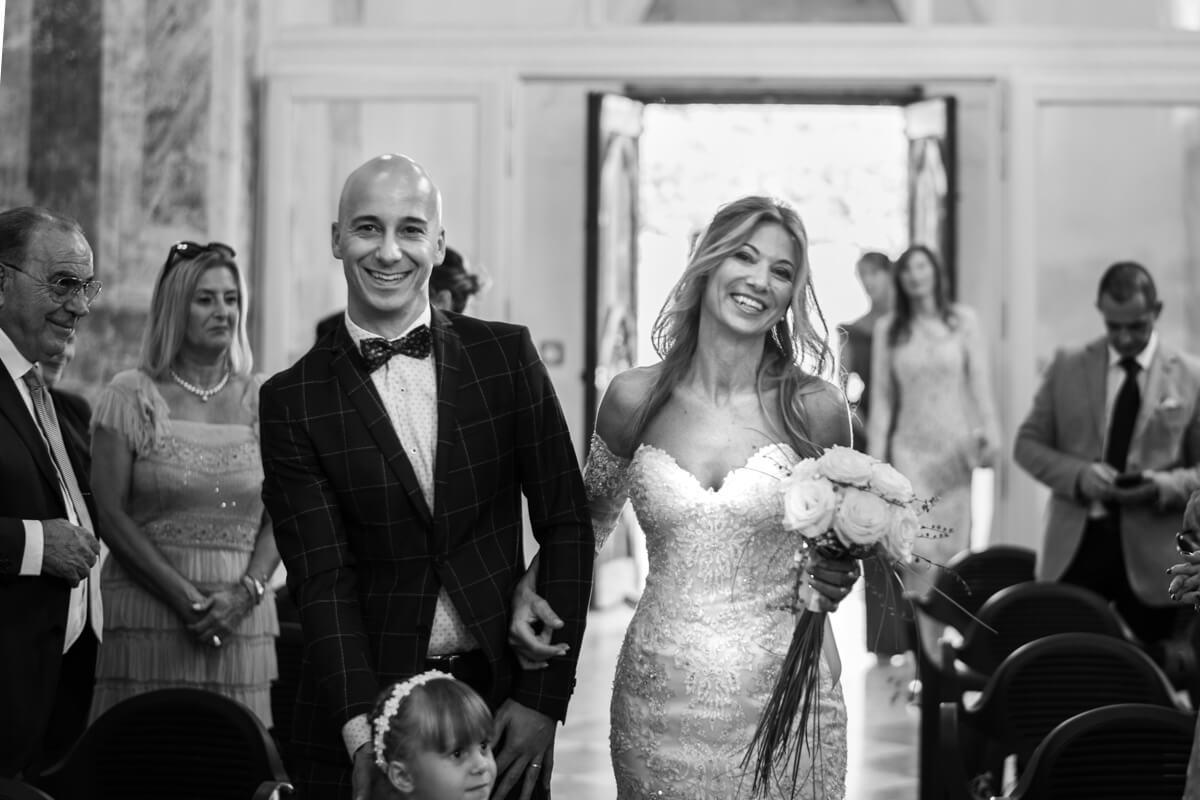 la sposa sorridente viene accompagnata all'altare dal fratello