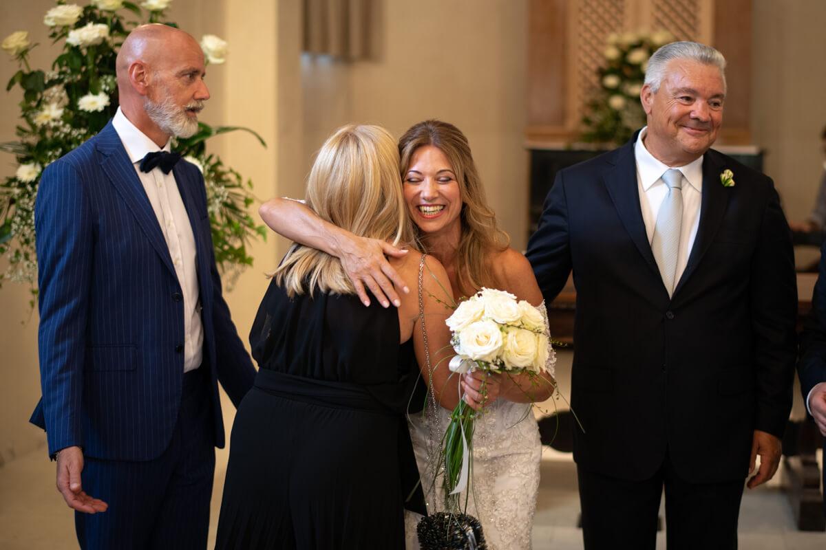 la sposa abbraccia un'amica alla fine della cerimonia in chiesa