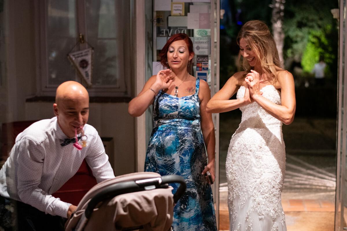la sposa si diverte insieme ad alcuni invitati con il bambino dentro la carrozzina