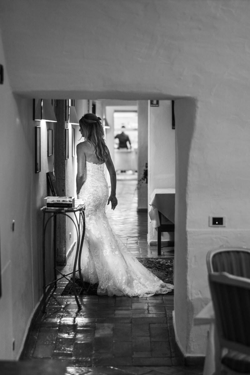 la sposa mentre corre si tiene l'abito con il lungo strascico
