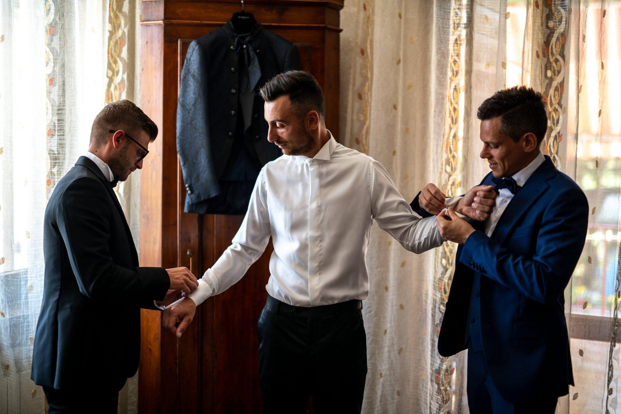 i testimoni aiutano lo sposo a vestirsi in preparazione al matrimonio