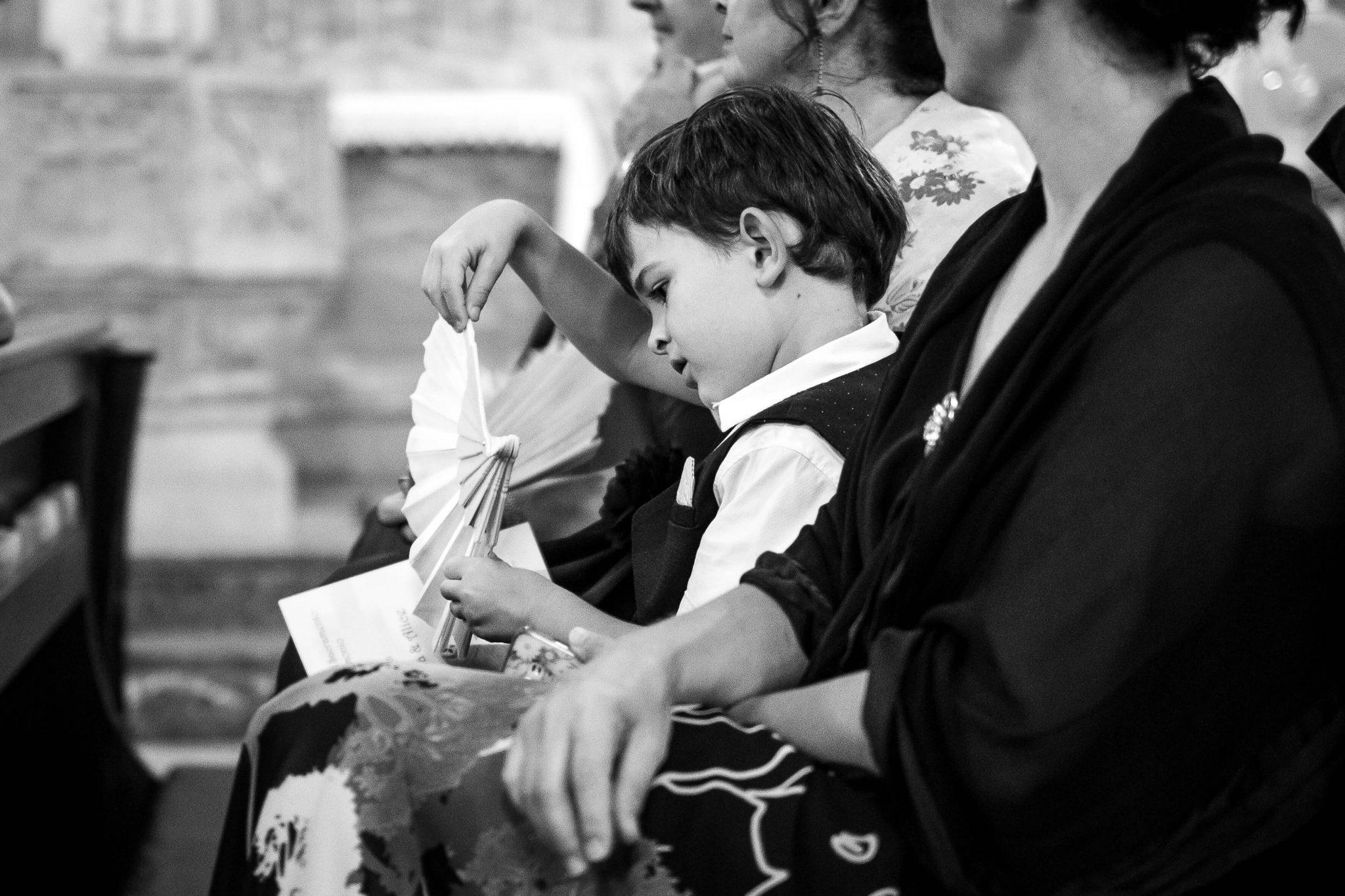 un bambino annoiato in chiesa gioca con un ventaglio
