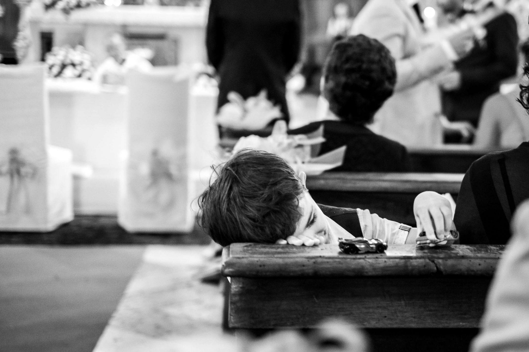 un bambino annoiato gioca in chiesa