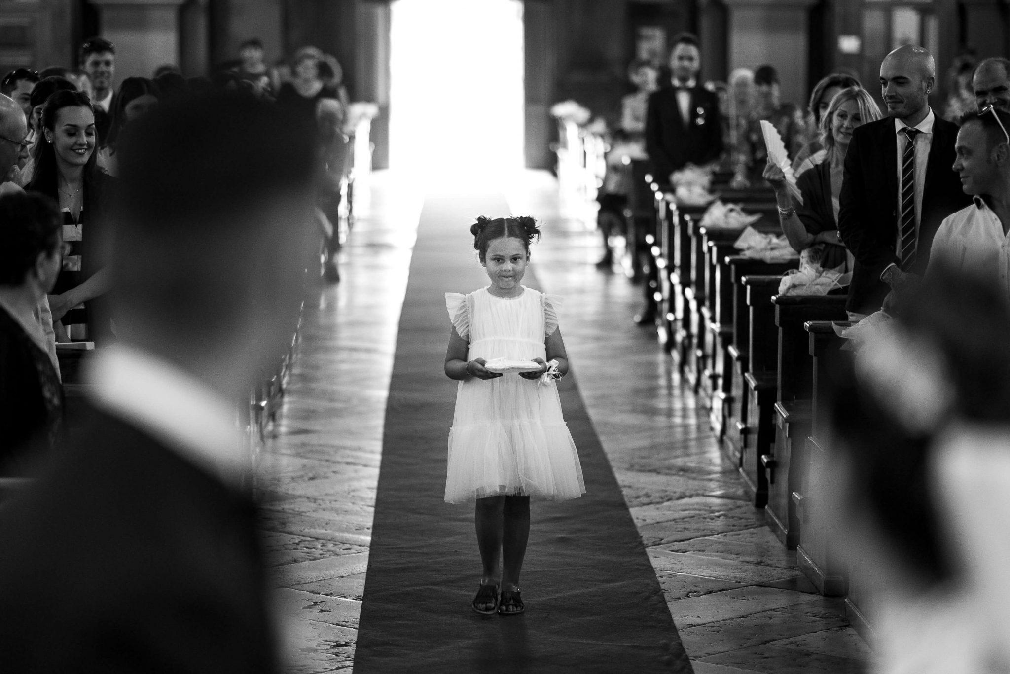 una bambina porta il cuscino con gli anelli all'altare