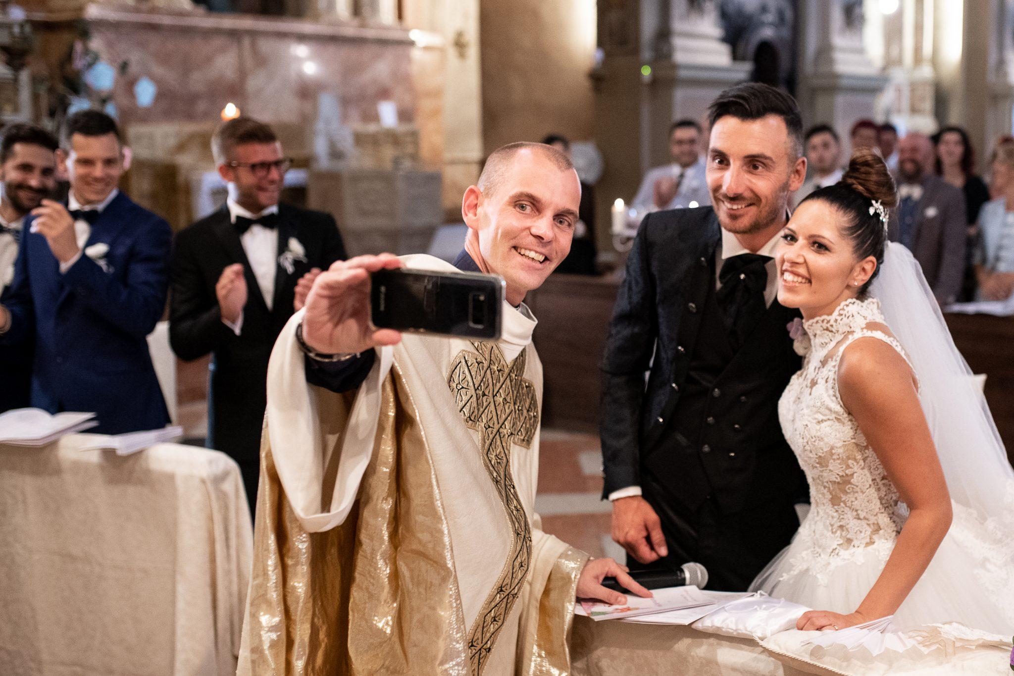 gli sposi insieme al parte si fanno un selfie davanti all'altare in chiesa