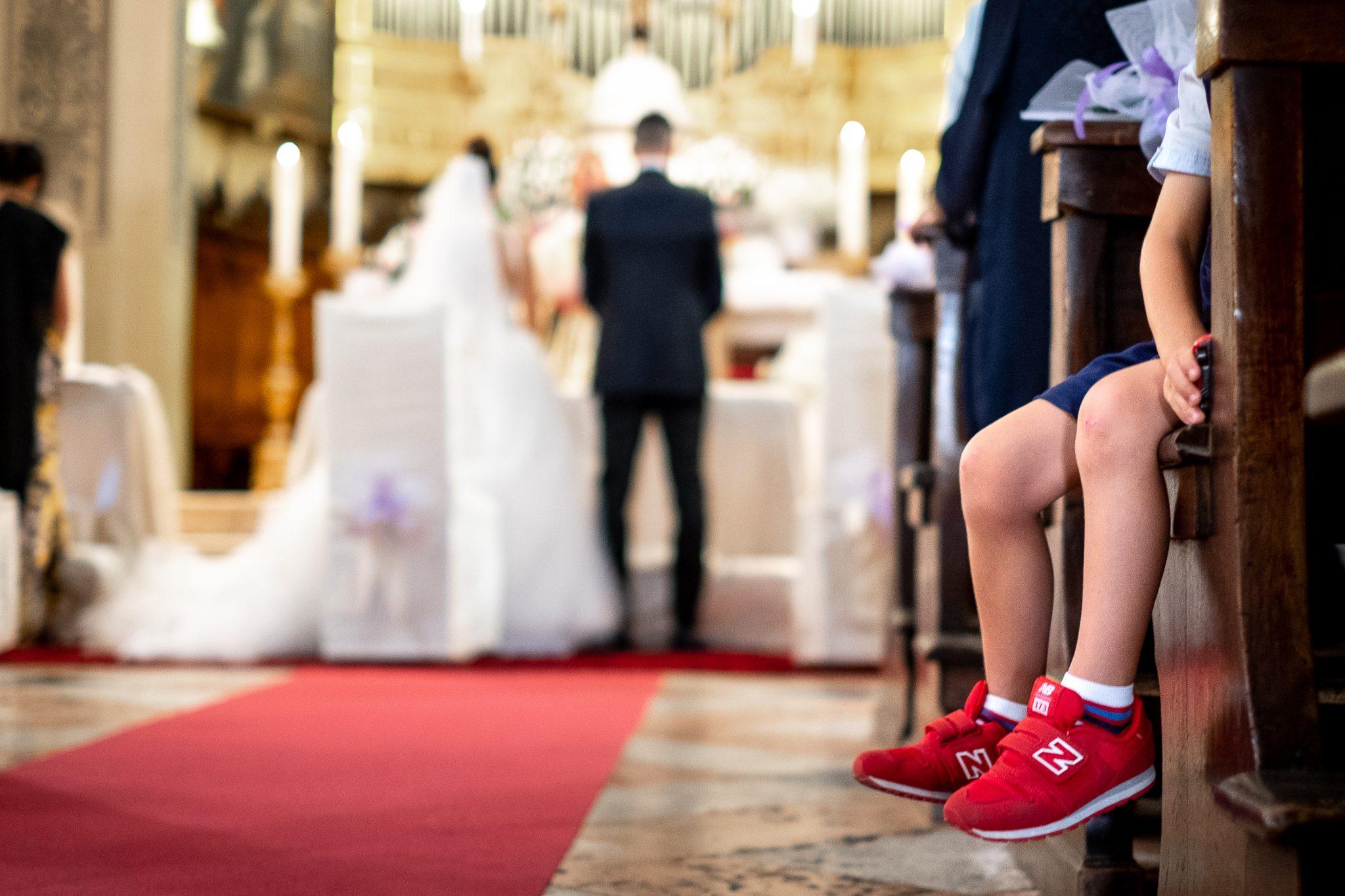 la scarpa di un bambino che sbuca da una panca della chiesa mentre gli sposi sono davanti all'altare
