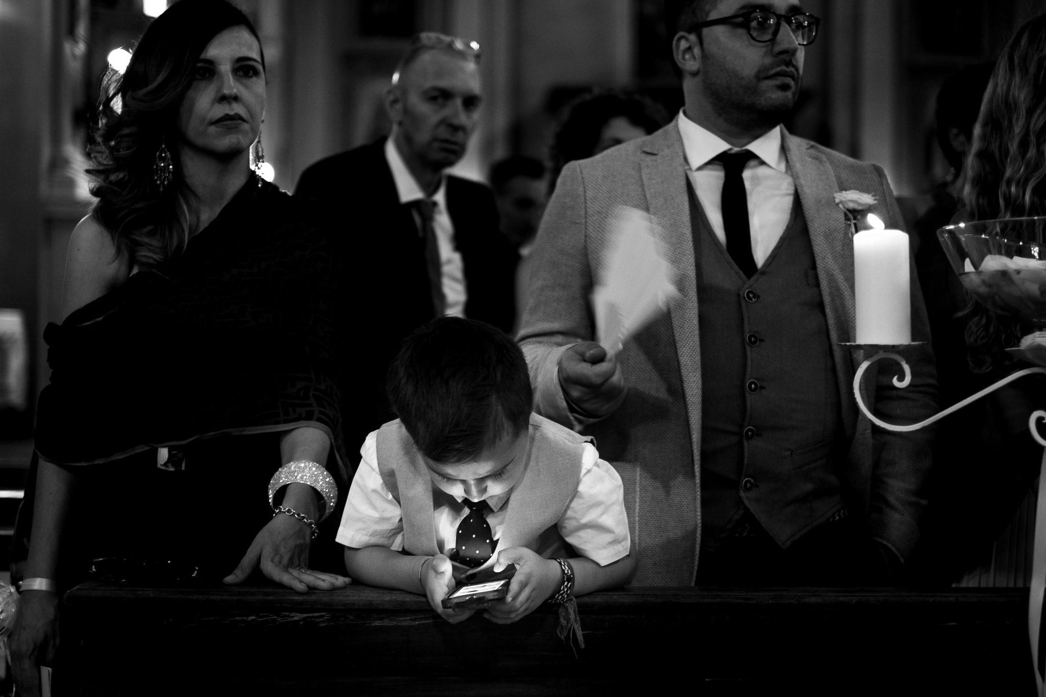 un bambino gioca con il telefono mentre gli invitati ascoltano la cerimonia