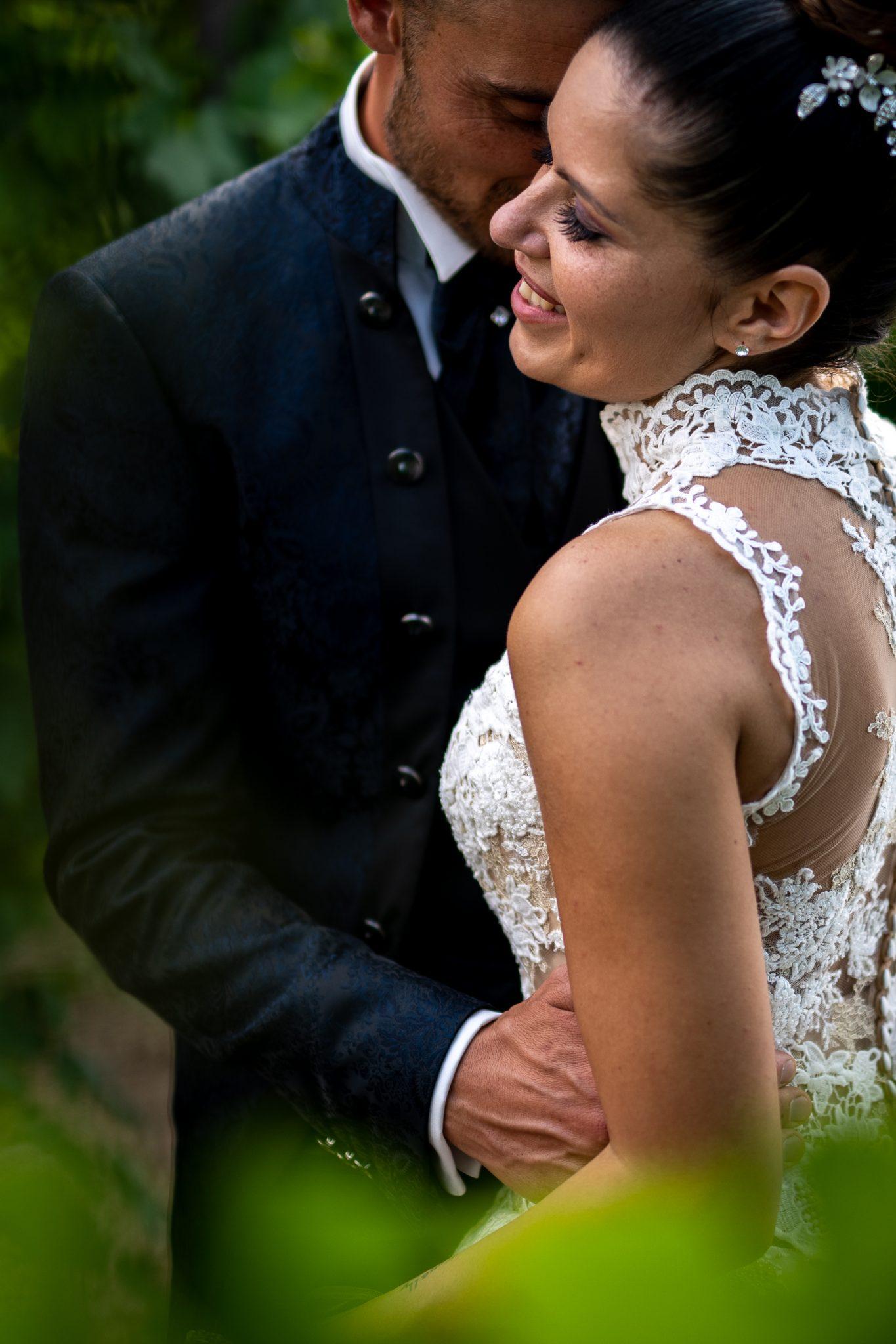 gli sposi nel giardino si abbracciano e sorridono