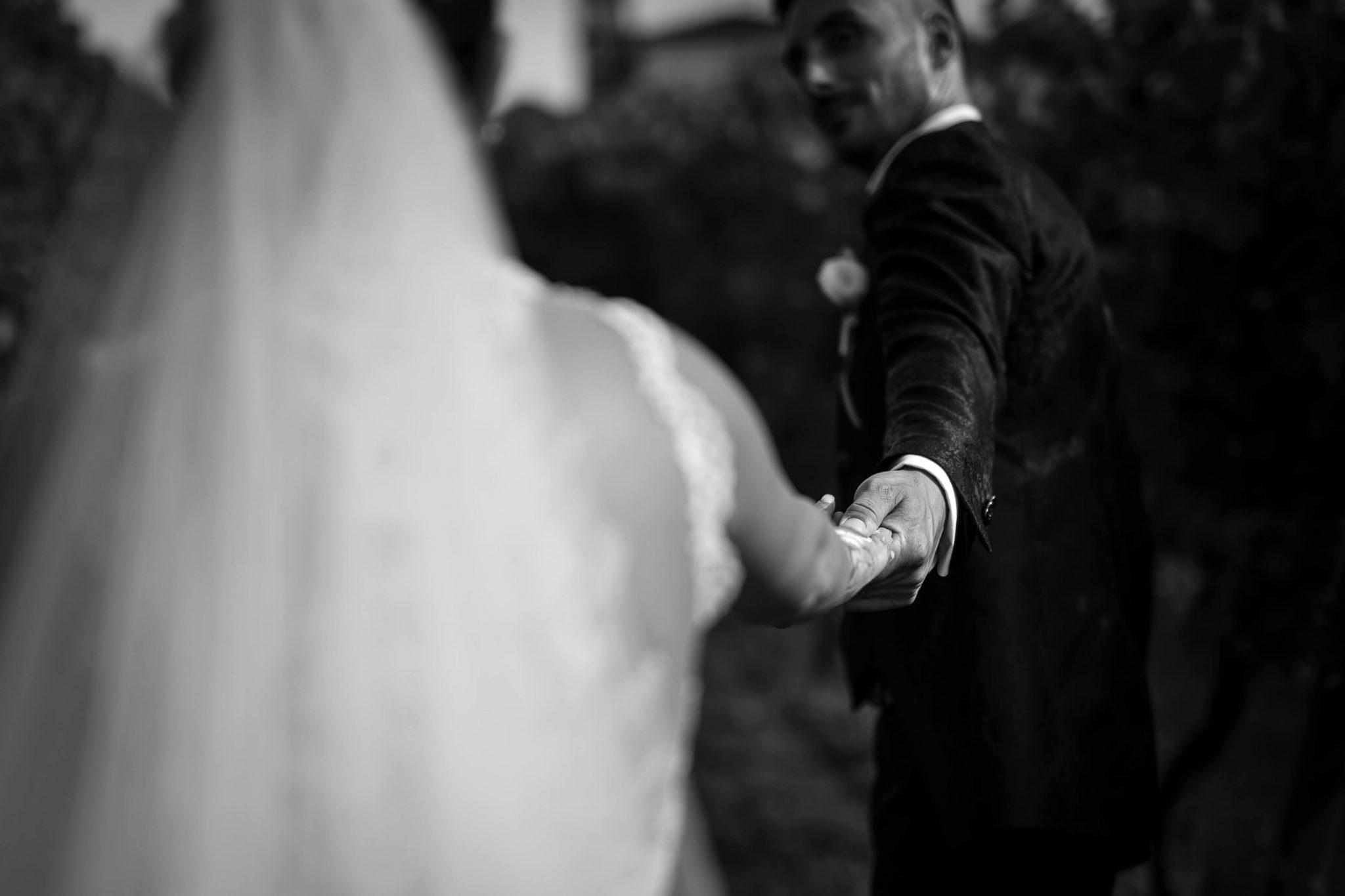 lo sposo guarda la sposa mentre la tiene per mano