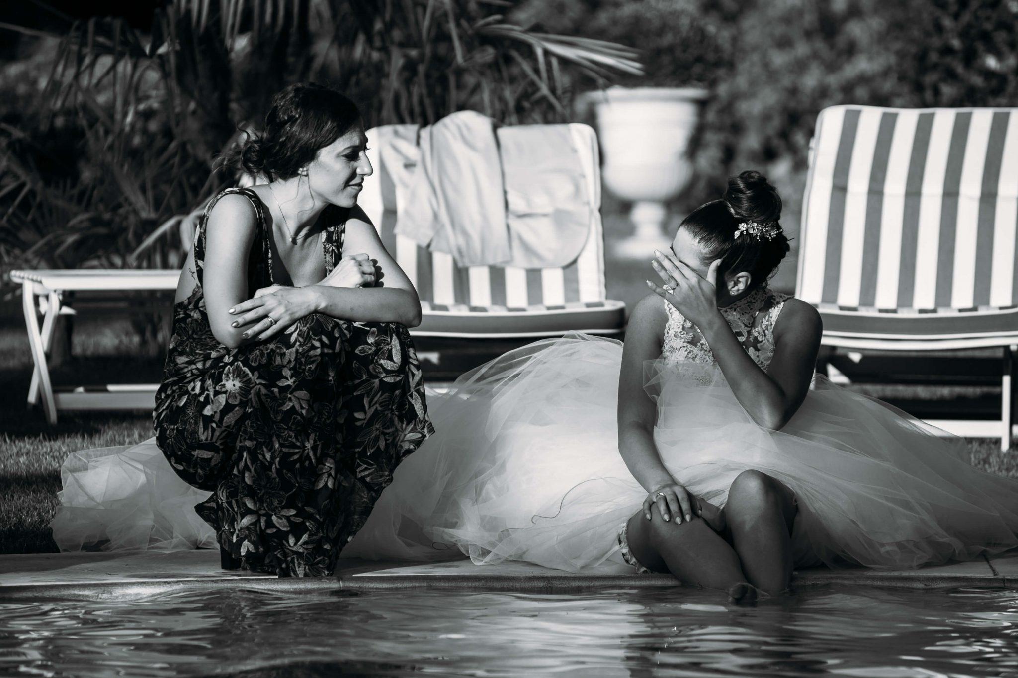 la sposa a bordo piscina chiacchiera con un'amica