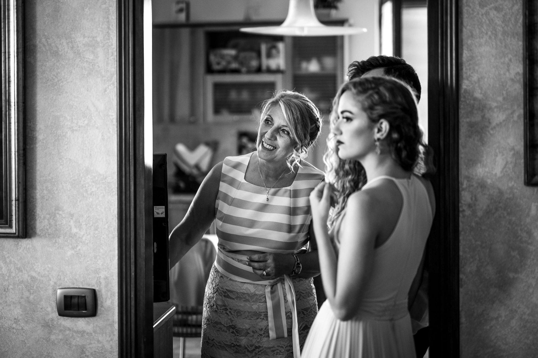 la mamma felice insieme ad alcuni invitati guarda lo sposo prepararsi
