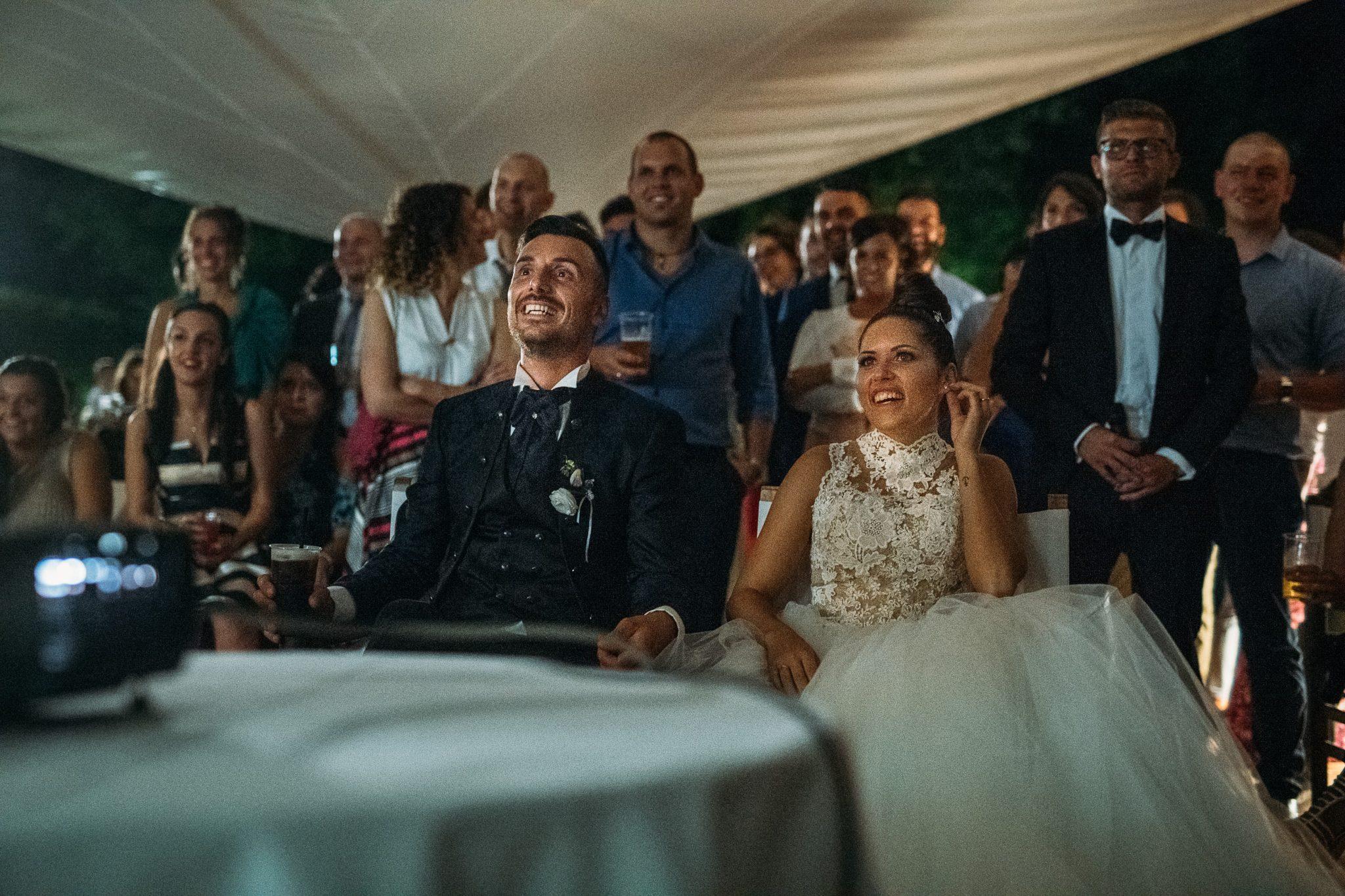 gli sposi seduti insieme agli invitati si divertono a guardare i video